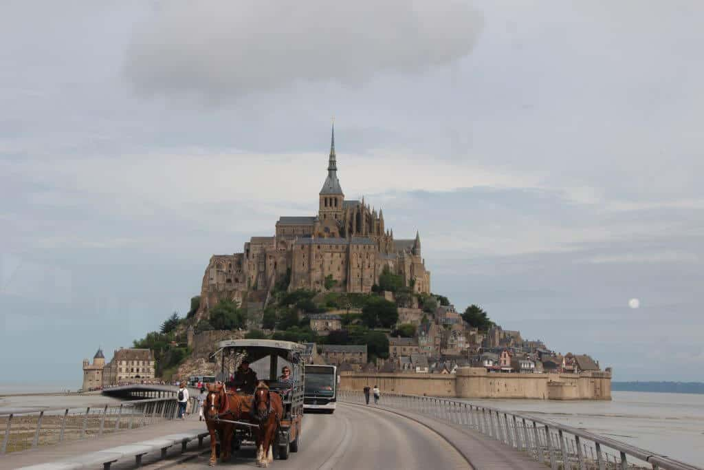 View of Mont Saint-Michel and the horse drawn carriage carrying people to the abbey.