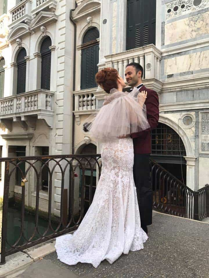 Woman in a wedding dress and man in a tux standing on a bridge in Venice, Itlay