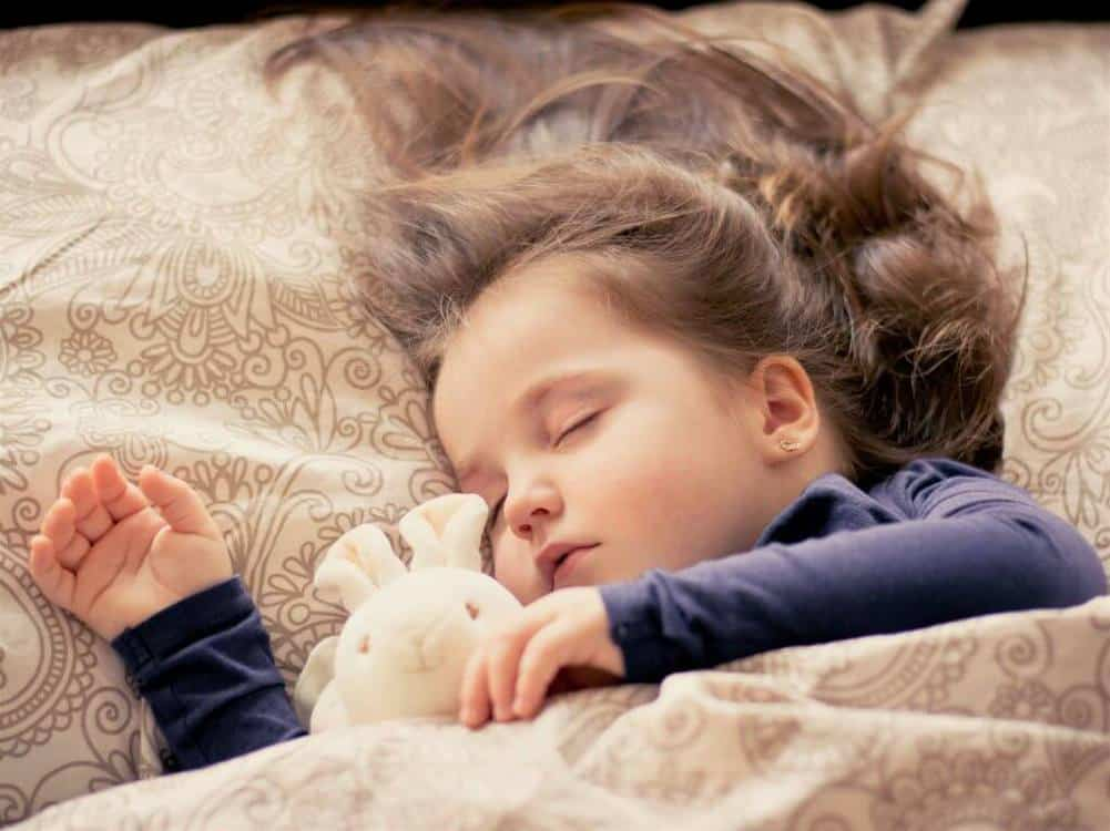 Child sleeping in a bed with a bear