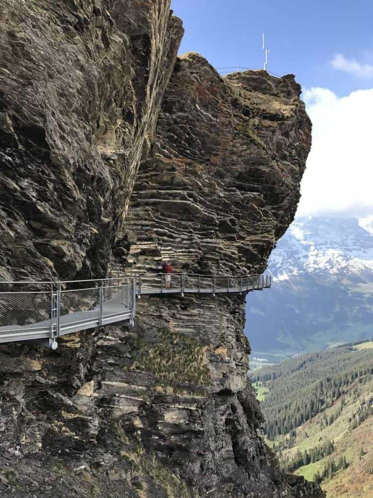 Grindelwald First Cliff walk showing a platform attached to the side of a cliff edge with a father and his son in a carrier standing on the platform.