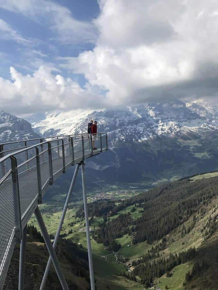 Grindelwald First Cliff walk. A platform with railings extending over the edge of the valley with a father and his son standing at the end.